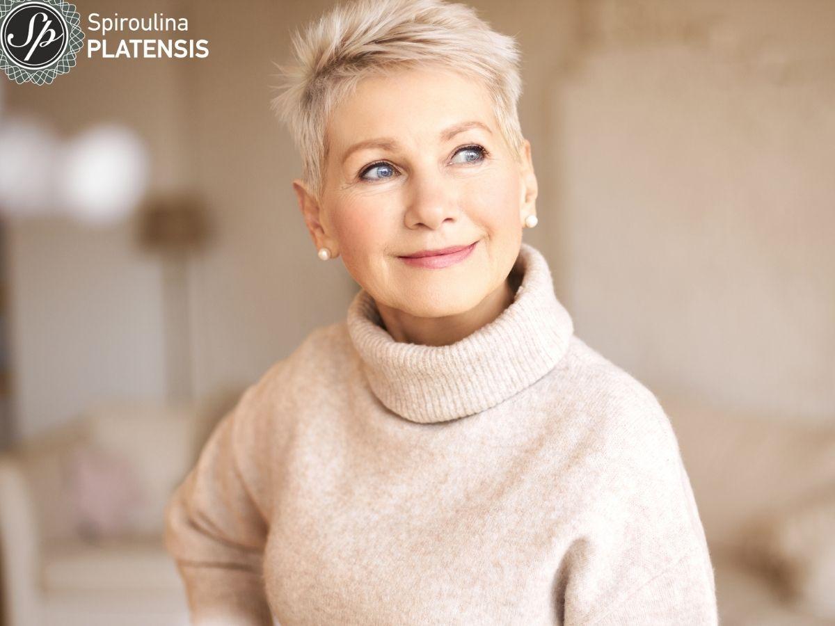 Ώριμη γυναίκα με κοντά γκρίζα μαλλιά και λαμπερό δέρμα που φοράει εκρού πουλόβερ