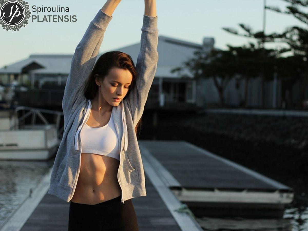 Νεαρή γυναίκα με αθλητικά ρούχα, λευκό μπουστάκι, αδύνατη κοιλιά με τα χέρια ψηλά