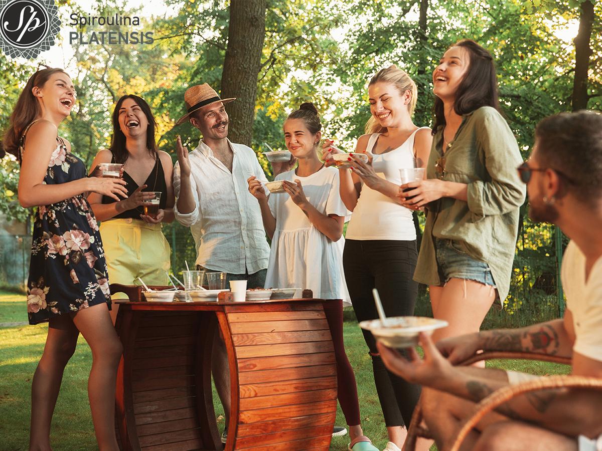Παρέα νέων ανθρώπων σε αυλή που πίνουν και τρώνε και γελάνε