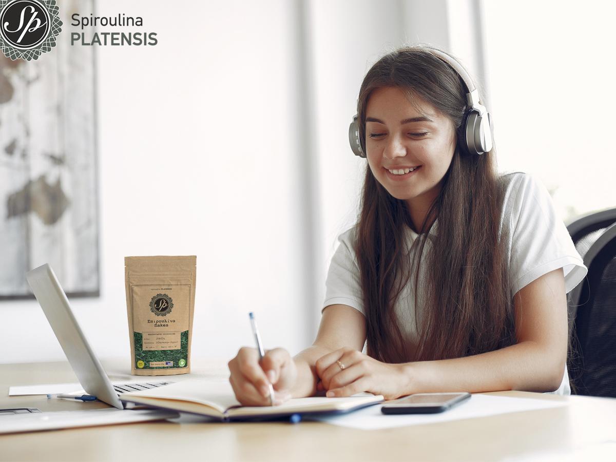 Νεαρή μαθήτρια με ακουστικά κάνει μάθημα και δίπλα υπάρχουν Σπιρουλίνα flakes