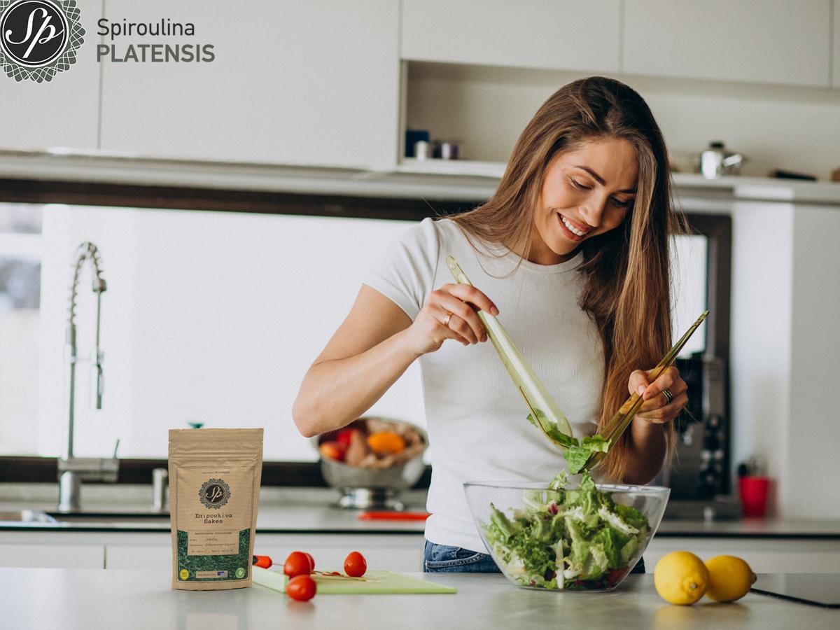Νεαρή γυναίκα με λευκό μπλουζάκι φτιάχνει σαλάτα και προσθέτει Σπιρουλίνα flakes