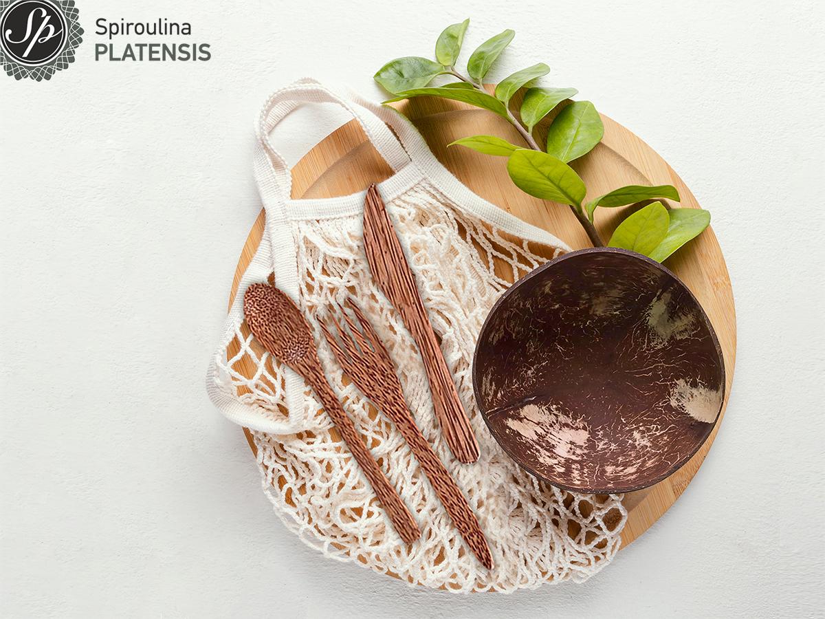 Στρογγυλός ξύλινος πάγκος κοπής που έχει πάνω μία πάνινη τσάντα, ένα coconut bowl, μαχαιροπίρουνα από κοκοφοίνικα