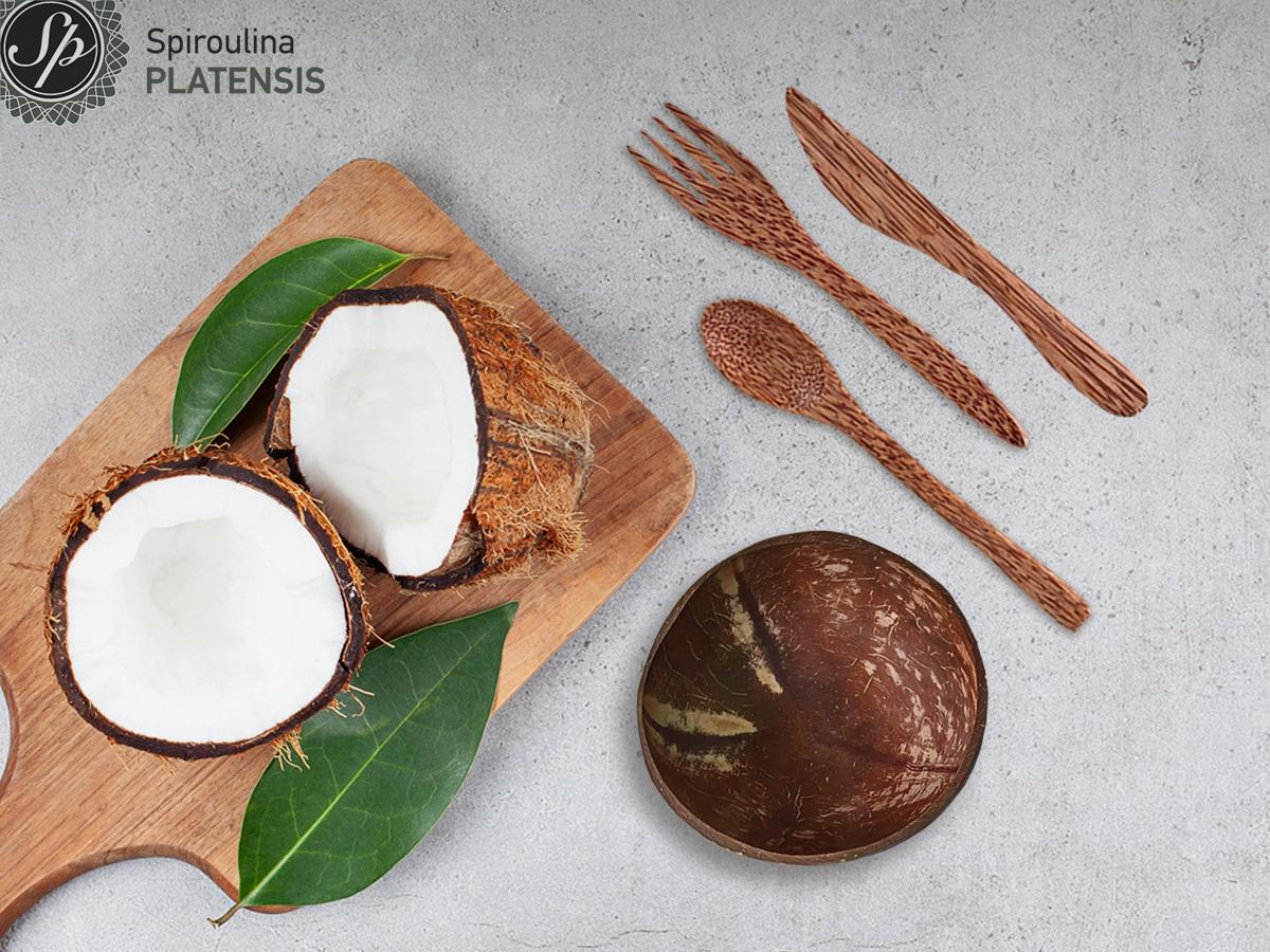 Μία καρύδα κομμένη στη μέση πάνω σε ξύλινο πάγκο και δίπλα ένα μπολ και μαχαιροπίρουνα από καρύδα