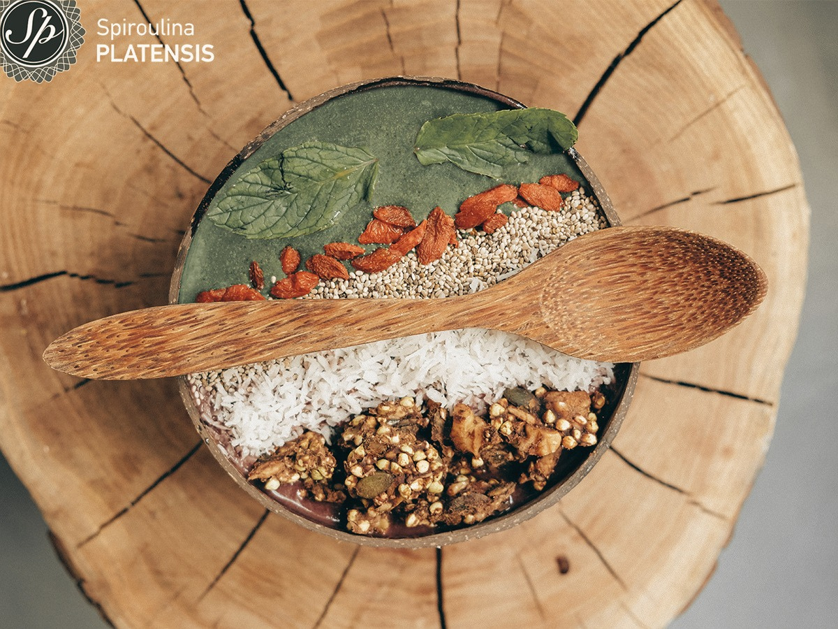 Acai bowl με Σκόνη Spiroulina PLATENSIS σε coconut bowl που είναι πάνω σε ένα ξύλο και πάνω στο μπολ υπάρχει ένα κουτάλι από κοκοφοίνικα