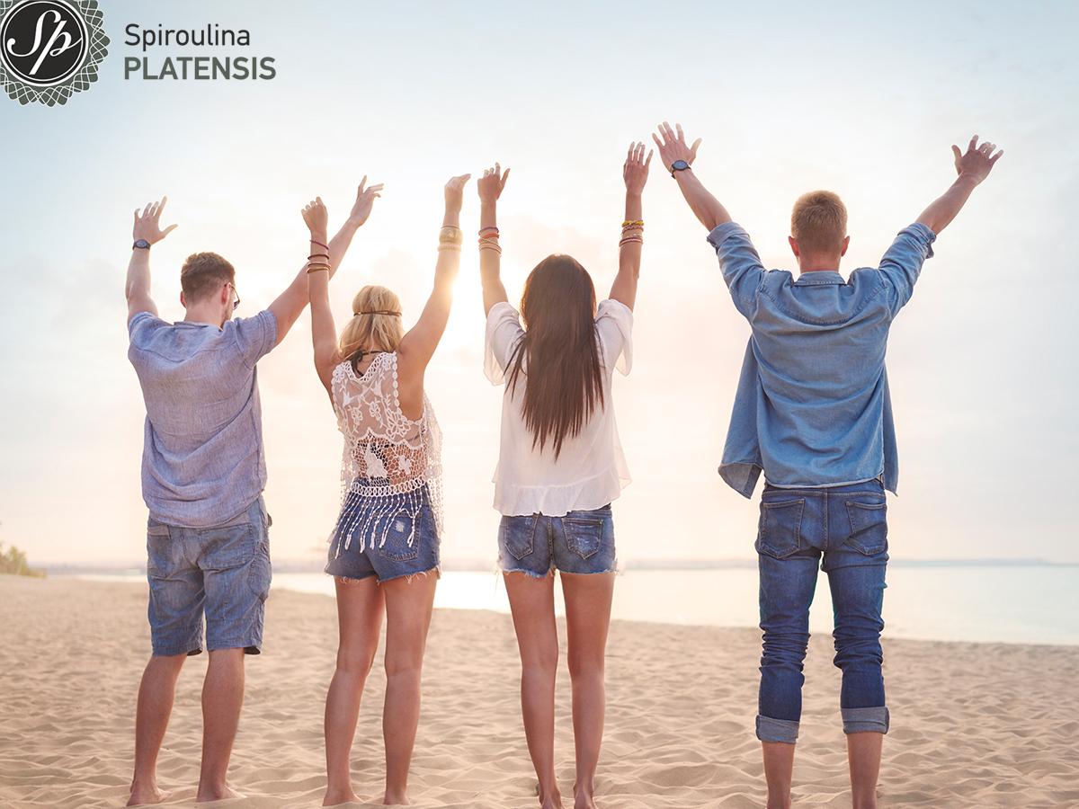 Μία παρέα από 2 αγόρια και 2 κορίτσια στην παραλία με τα χέρια ψηλά