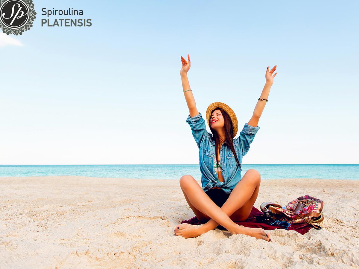 Κοπέλα με τα χέρια ψηλα στην παραλία