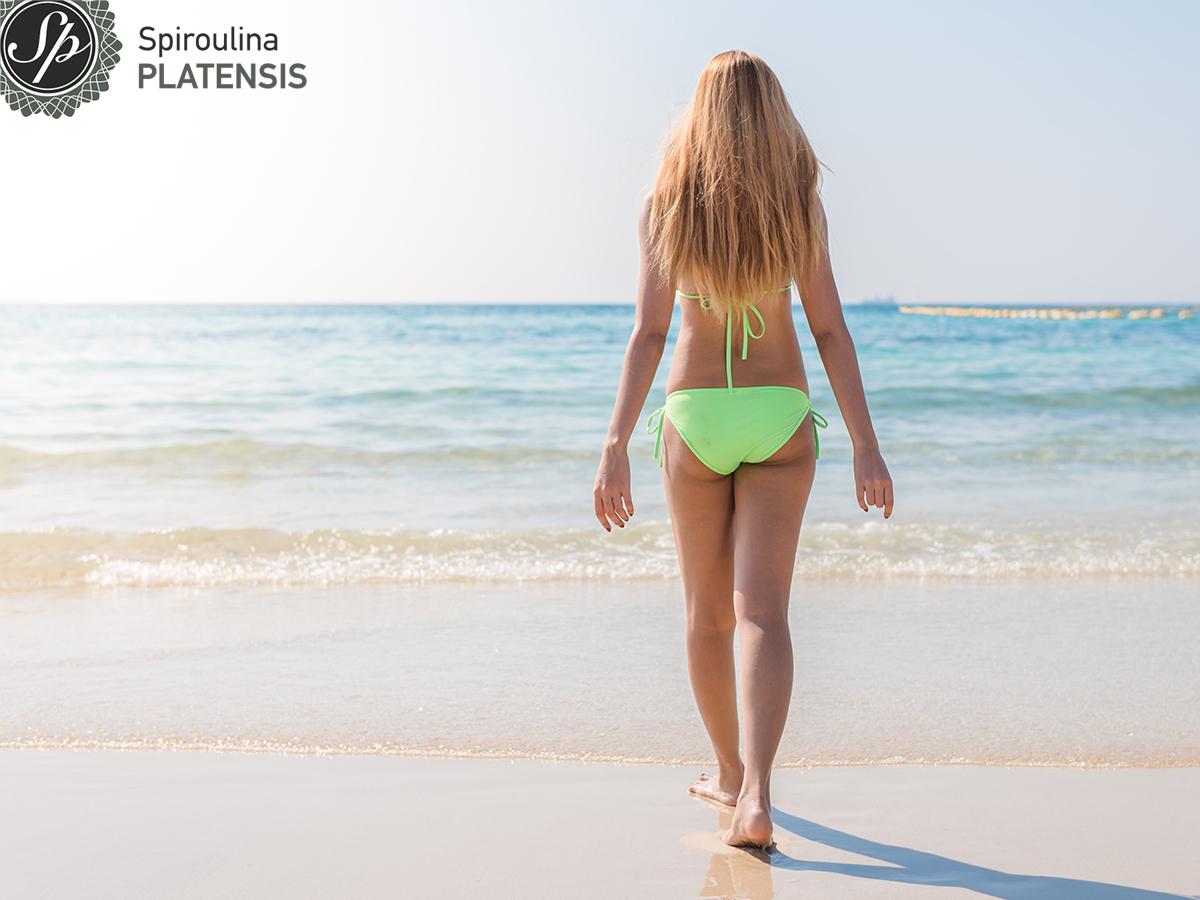 Νεαρή γυναίκα που περπατάει προς την παραλία με πράσινο μαγιό