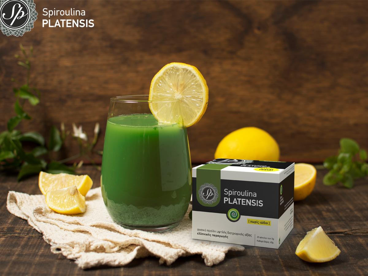 Ποτήρι με πράσινο smoothie, πορτοκάλια και ένα κουτί σκόνη Spiroulina PLATENSIS