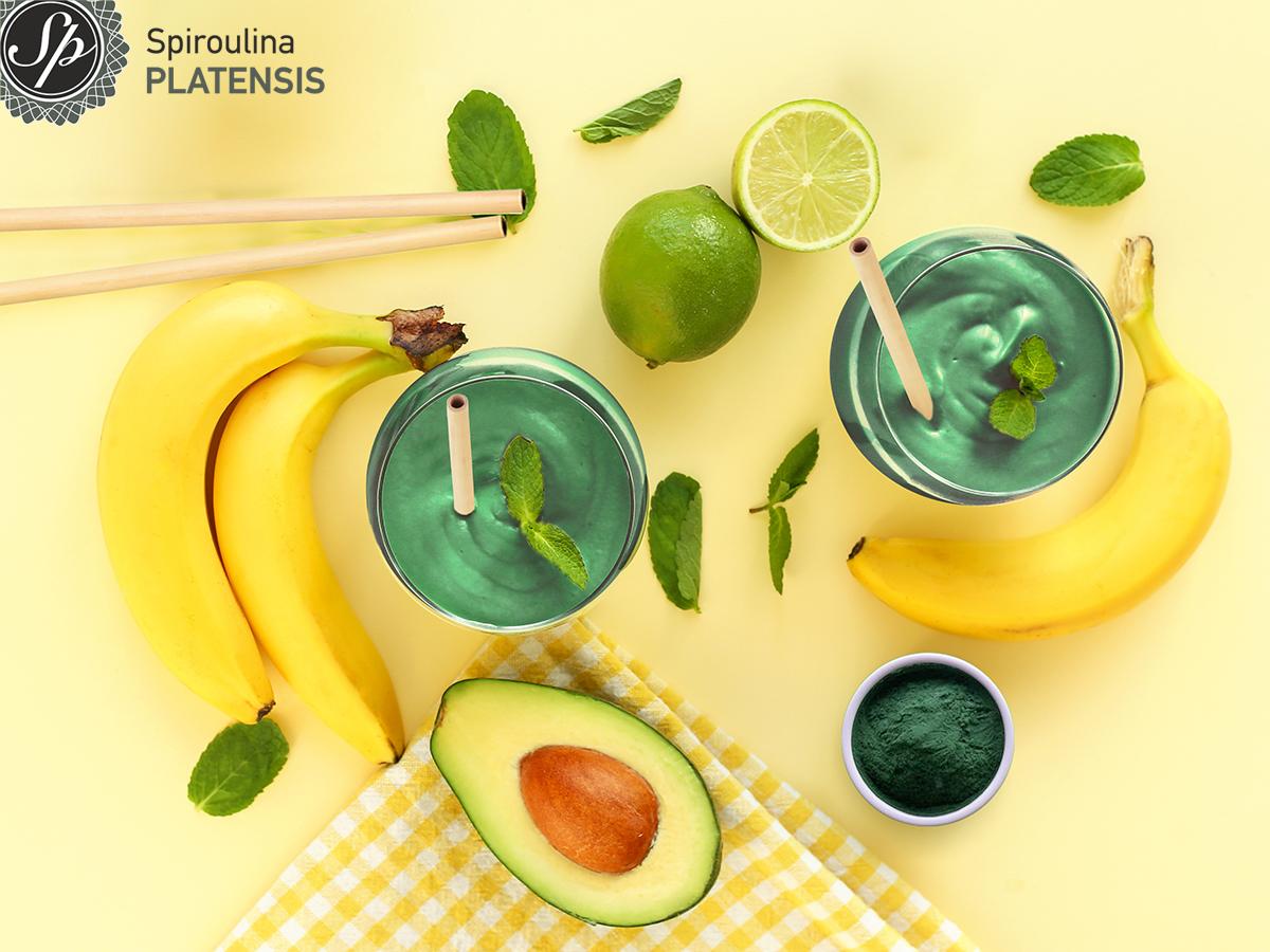 Δύο ποτήρια πράσινο smoothie που γύρω τους έχουν μπανάνες, αβοκάντο, lime και Σκόνη Spiroulina PLATENSIS
