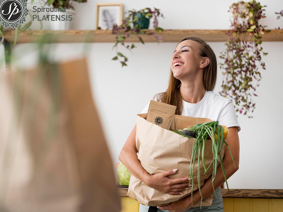 Κοπέλα που χαμογελάει και κρατάει χάρτινη σακούλα με φυσικά προϊόντα