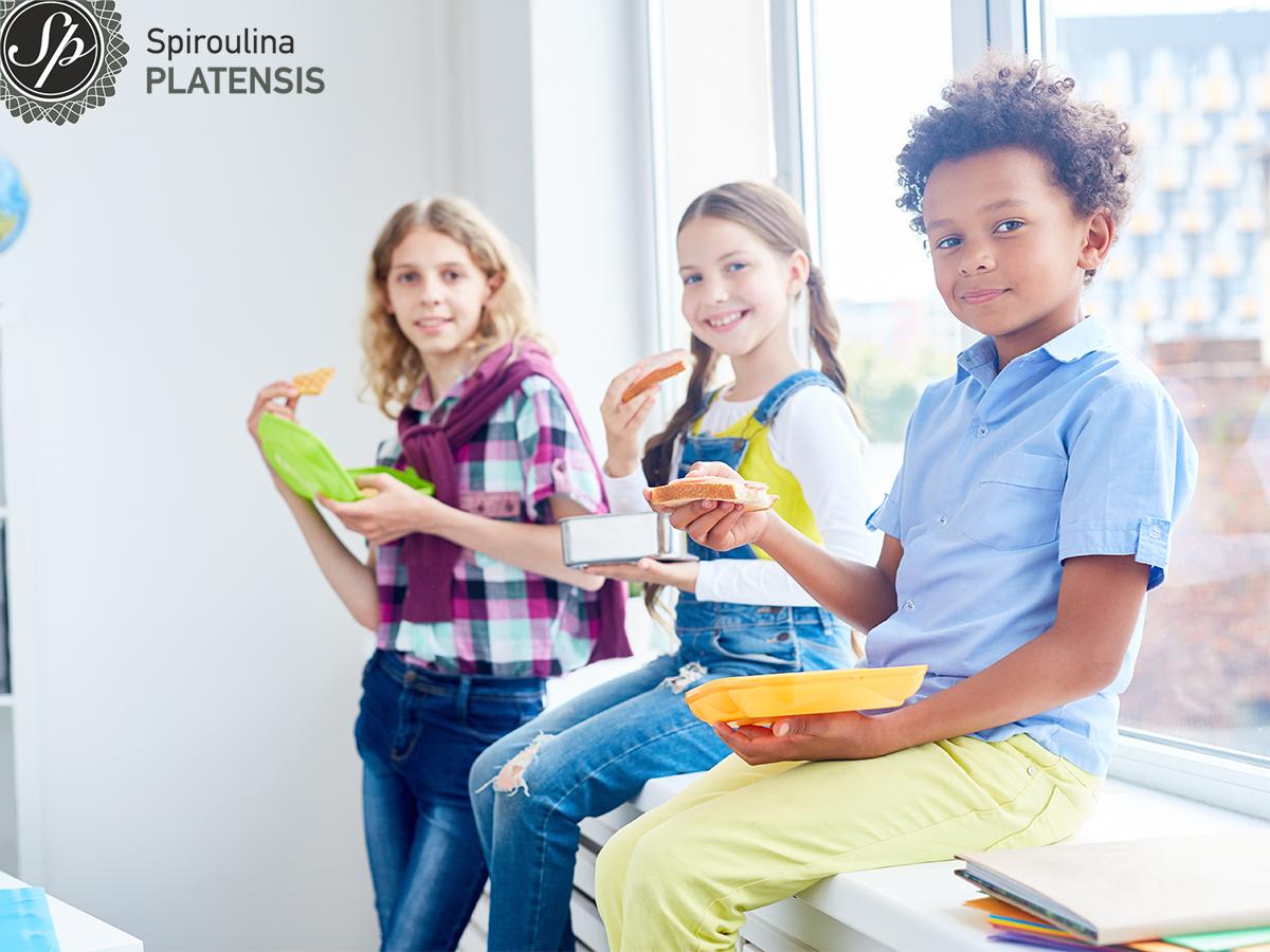 3 παιδιά στο σχολείο που ετοιμάζονται να φάνε το κολατσιό τους