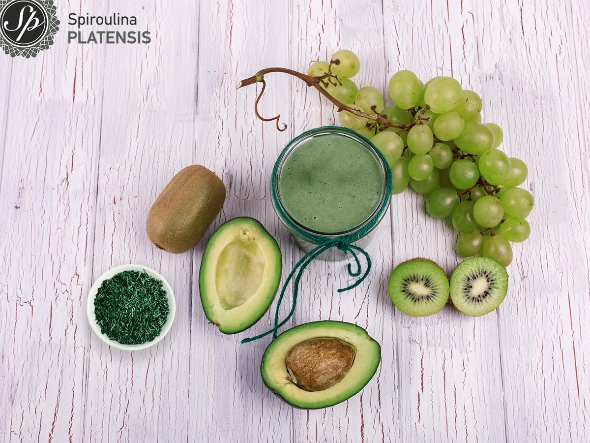 Ποτήρι με πράσινο smoothie και γύρω του ένα μπολάκι Σπιρουλίνα flakes, ένα αβοκάντο, ένα τσαμπί σταφύλι και ακτινίδια