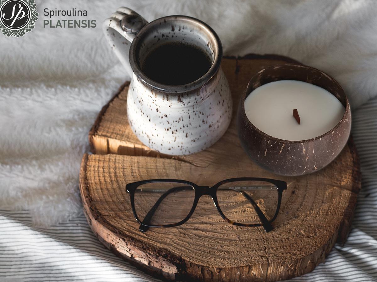 Ένας δίσκος από κορμό δέντρου που πάνω έχει μία κούπα καφέ, ένα ζευγάρι γυαλιά οράσεως και ένα Coconut candle