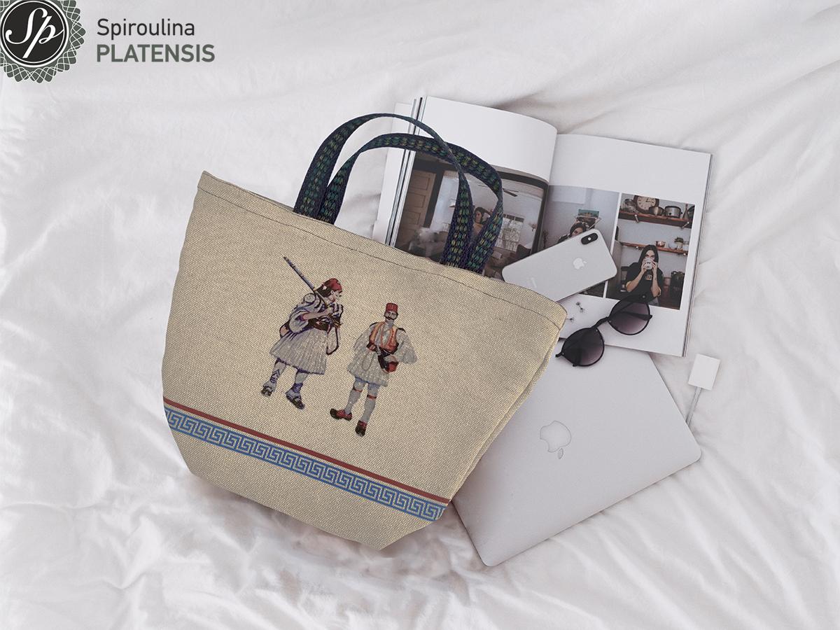Evzones bag πάνω σε κρεβάτι με λευκό σεντόνι ένα iphone & macbook δίπλα