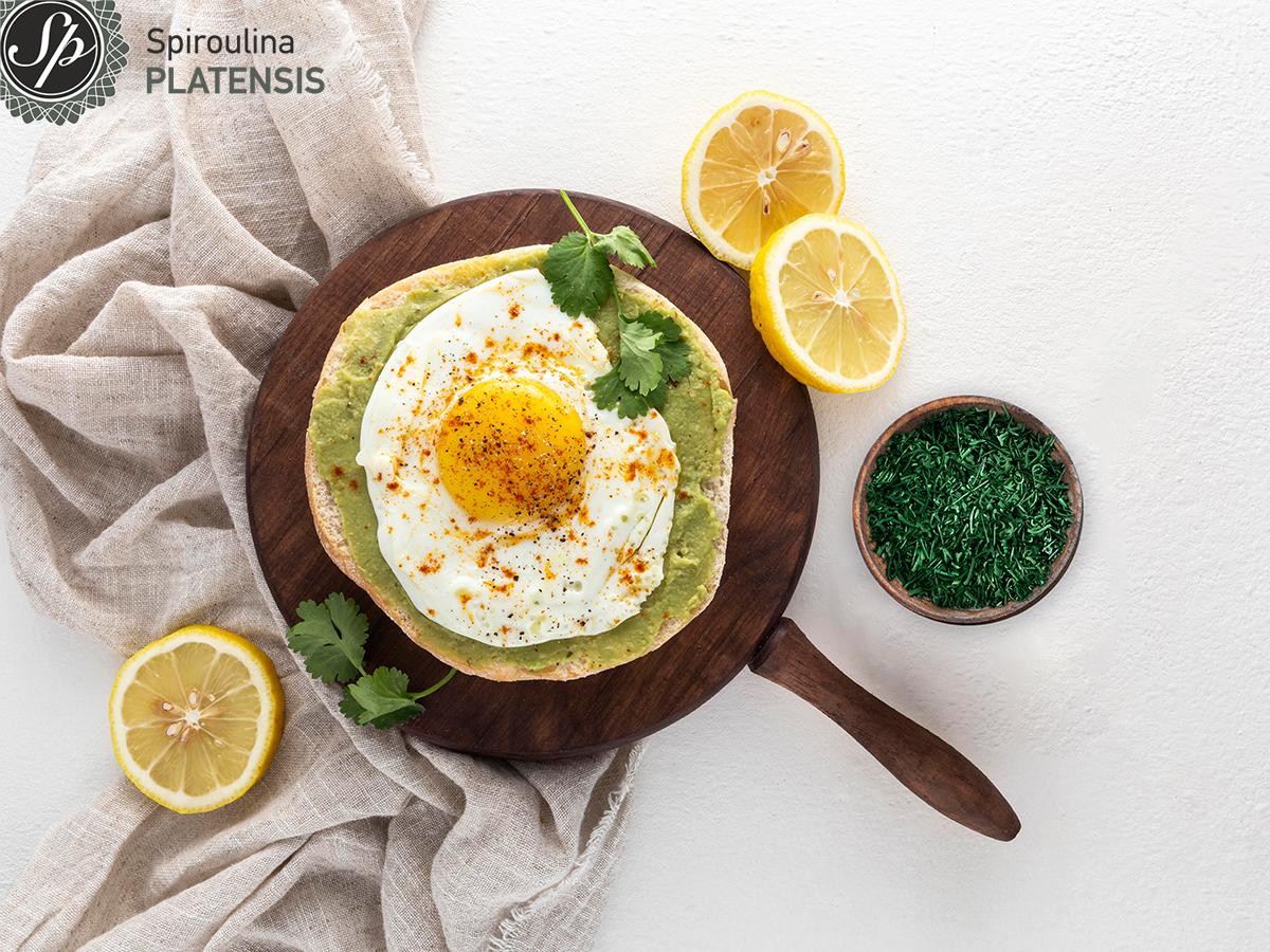 Πίτα με αυγό, αβοκάντο, Σπιρουλίνα flakes σε ξύλινη βάση